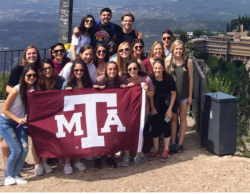 Students on hill with A&M flag