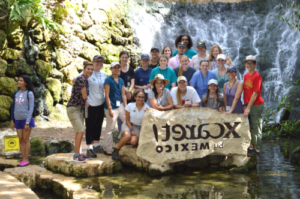 Group photo in front of waterfall and Xcaret Mexico sign