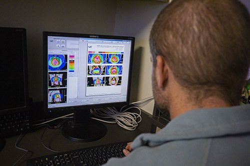 Radiation oncologist Dr. Michael Deveau watches a screen of colorful scans to monitor Lady as she undergoes her TomoTherapy treatment